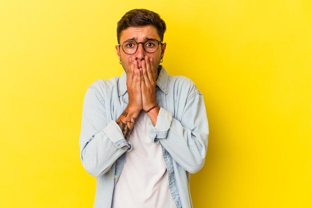 Jovem homem caucasiano com tatuagens isoladas em fundo amarelo, cobrindo a boca com as mãos parecendo preocupado.
