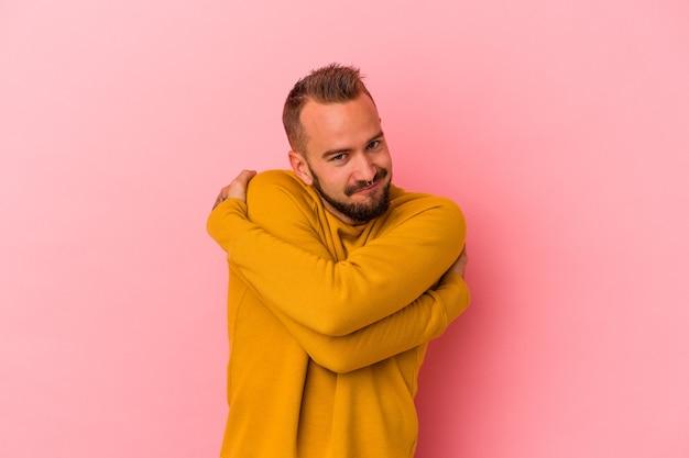Jovem homem caucasiano com tatuagens isoladas em um fundo rosa abraços, sorrindo despreocupado e feliz.