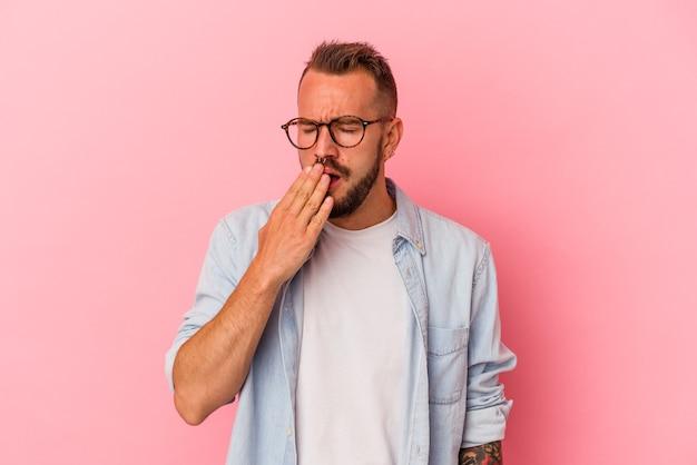 Jovem homem caucasiano com tatuagens isoladas em um fundo rosa, bocejando, mostrando um gesto cansado, cobrindo a boca com a mão.