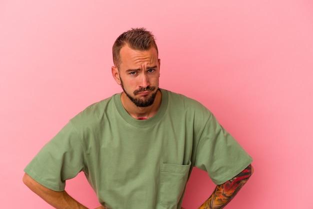 Jovem homem caucasiano com tatuagens isoladas em um fundo rosa confuso, sente-se duvidoso e inseguro.