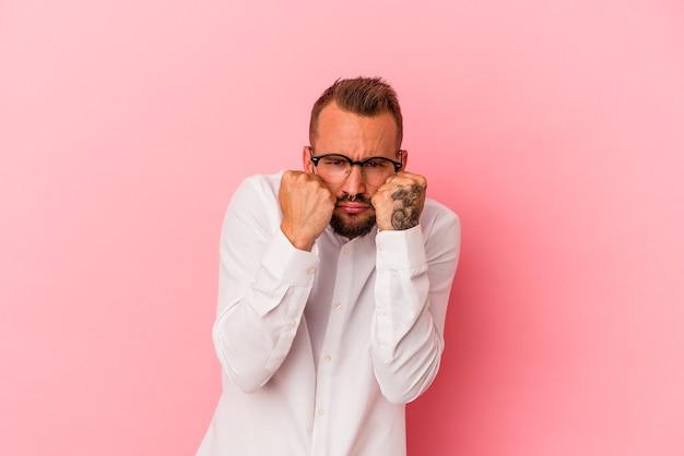 Jovem homem caucasiano com tatuagens isoladas em um fundo rosa, dando um soco, raiva, lutando devido a uma discussão, boxe.