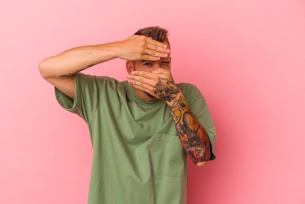 Jovem homem caucasiano com tatuagens isoladas em um fundo rosa pisca para a câmera por entre os dedos, o rosto coberto de vergonha.
