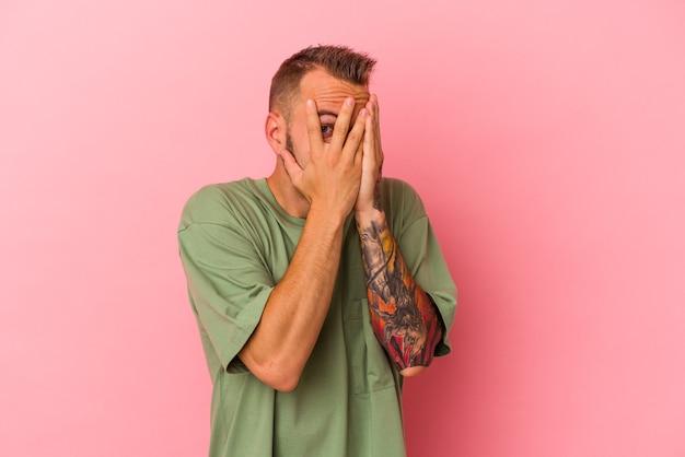 Jovem homem caucasiano com tatuagens isoladas em um fundo rosa piscar por entre os dedos assustado e nervoso.