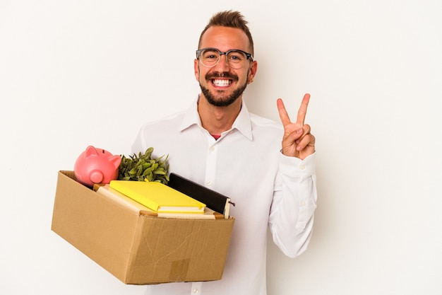 Jovem homem caucasiano com tatuagens, mudando para casa, isolado no fundo branco, mostrando o número dois com os dedos.
