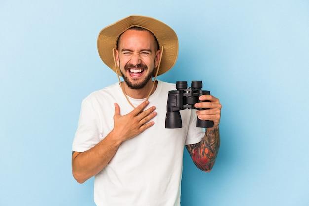 Jovem homem caucasiano com tatuagens segurando binóculos isolados em fundo azul ri alto mantendo a mão no peito.