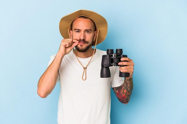 Jovem homem caucasiano com tatuagens segurando binóculos isolados em um fundo azul com os dedos nos lábios, mantendo um segredo.
