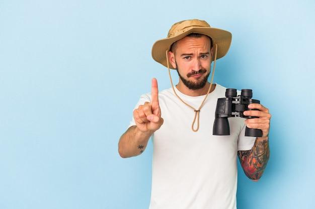 Jovem homem caucasiano com tatuagens segurando binóculos isolados em um fundo azul, mostrando o número um com o dedo.
