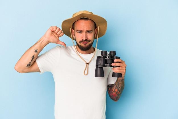 Jovem homem caucasiano com tatuagens segurando binóculos isolados em um fundo azul se sente orgulhoso e autoconfiante, exemplo a seguir.