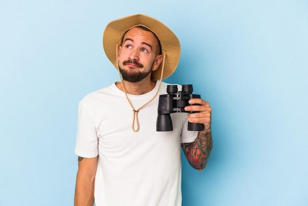 Jovem homem caucasiano com tatuagens segurando binóculos isolados em um fundo azul, sonhando em alcançar objetivos e propósitos