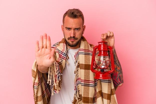 Jovem homem caucasiano com tatuagens segurando lanterna vintage isolada no fundo rosa em pé com a mão estendida, mostrando o sinal de pare, impedindo você.