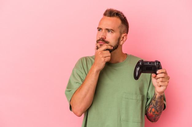 Jovem homem caucasiano com tatuagens segurando o controlador de jogo isolado no fundo rosa, olhando de soslaio com expressão duvidosa e cética.