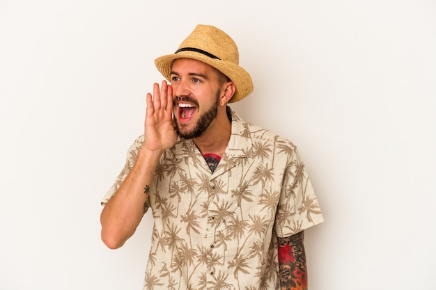 Jovem homem caucasiano com tatuagens, vestindo roupas de verão, isoladas no fundo branco, gritando e segurando a palma da mão perto da boca aberta.