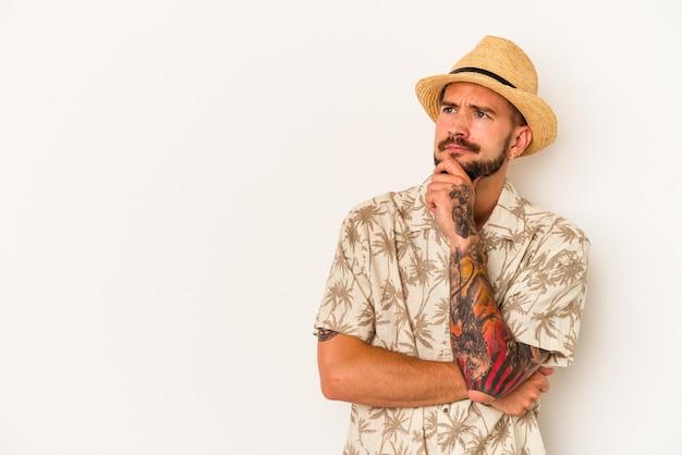 Jovem homem caucasiano com tatuagens, vestindo roupas de verão, isoladas no fundo branco, olhando de soslaio com expressão duvidosa e cética.