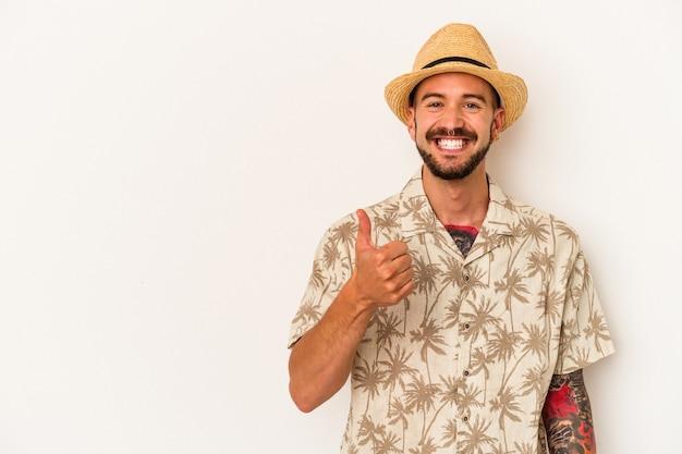 Jovem homem caucasiano com tatuagens, vestindo roupas de verão, isoladas no fundo branco, sorrindo e levantando o polegar