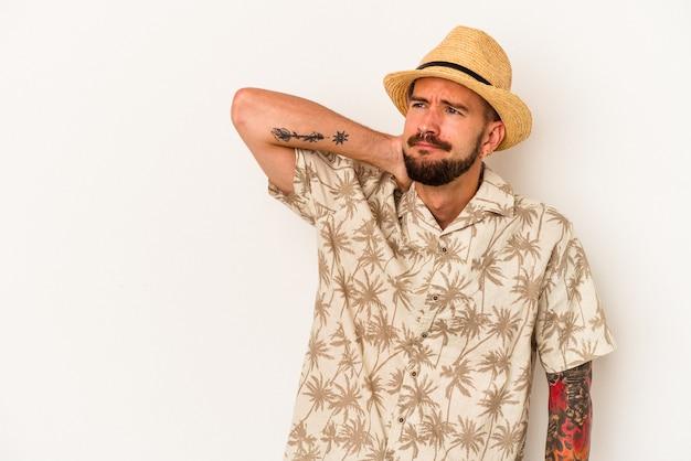 Jovem homem caucasiano com tatuagens, vestindo roupas de verão, isoladas no fundo branco, tocando a nuca, pensando e fazendo uma escolha.