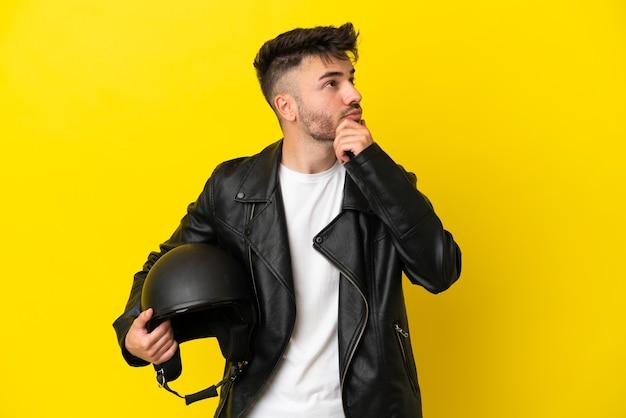 Jovem homem caucasiano com um capacete de motociclista isolado em um fundo amarelo e olhando para cima