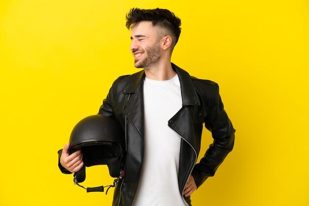 Jovem homem caucasiano com um capacete de motociclista isolado em um fundo amarelo, sofrendo de dor nas costas por ter feito um esforço