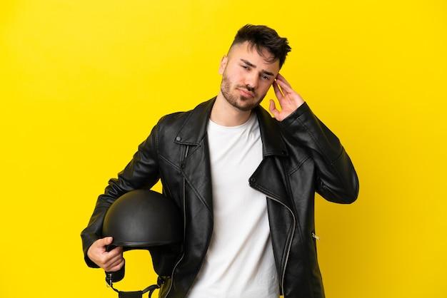 Jovem homem caucasiano com um capacete de motociclista isolado em um fundo amarelo, tendo dúvidas