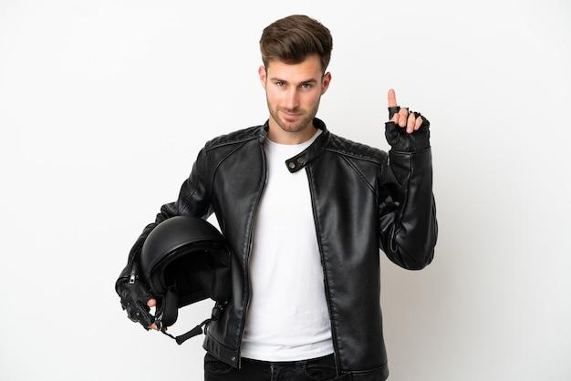 Jovem homem caucasiano com um capacete de motociclista isolado no fundo branco apontando para uma ótima ideia