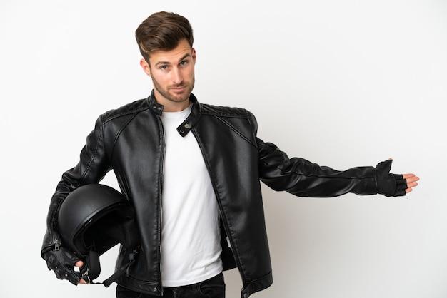 Jovem homem caucasiano com um capacete de motociclista isolado no fundo branco, estendendo as mãos para o lado para convidar para vir