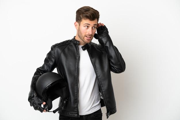 Jovem homem caucasiano com um capacete de motociclista isolado no fundo branco, ouvindo algo colocando a mão na orelha