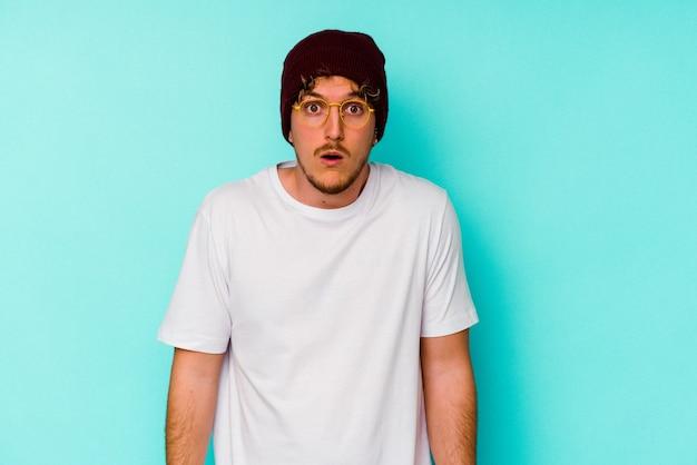 Jovem homem caucasiano com um chapéu de lã isolado no fundo azul encolhe os ombros e abre os olhos confusos.