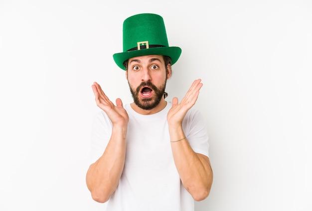 Jovem homem caucasiano com um chapéu de saint patrick isolado surpreso e chocado.