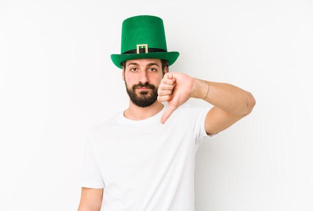 Jovem homem caucasiano com um chapéu de saint patricks isolado, mostrando um gesto de antipatia, polegares para baixo. conceito de desacordo.