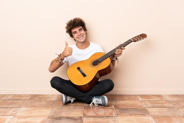 Jovem homem caucasiano com um violão sentado no chão com os polegares para cima, porque algo de bom aconteceu