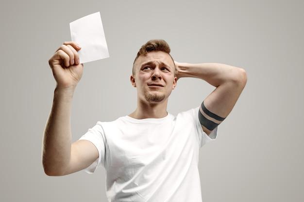 Jovem homem caucasiano com uma expressão de felicidade e surpresa ganhou uma aposta no espaço cinza