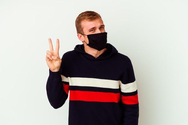 Jovem homem caucasiano com uma máscara para vírus isolado no branco, mostrando sinal de vitória e sorrindo amplamente.