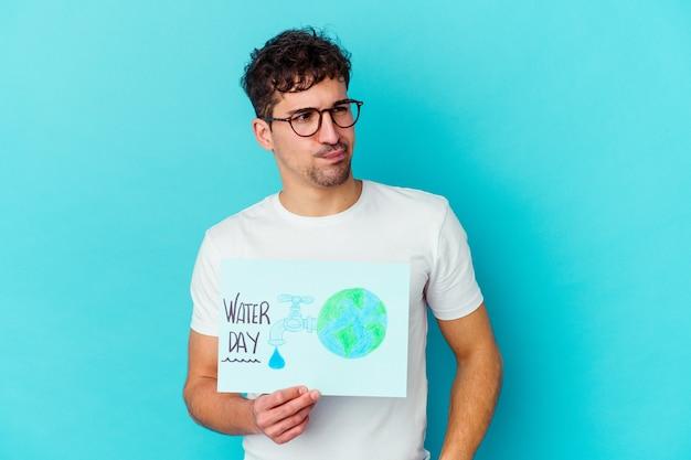Jovem homem caucasiano comemorando o dia mundial da água isolado, confuso, sente-se em dúvida e inseguro.