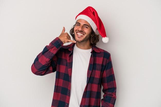 Jovem homem caucasiano comemorando o natal isolado em um fundo cinza, mostrando um gesto de chamada de celular com os dedos.