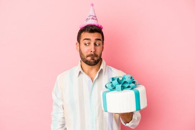 Jovem homem caucasiano comemorando seu aniversário isolado em um fundo rosa confuso, sente-se duvidoso e inseguro.