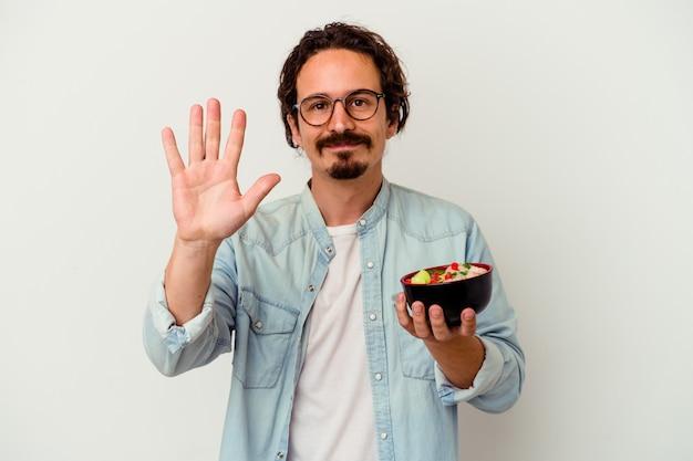 Jovem homem caucasiano comendo um ramen sorrindo alegre mostrando o número cinco com os dedos.