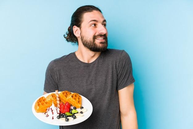 Jovem homem caucasiano comendo uma sobremesa waffle isolado, sonhando em alcançar objetivos e propósitos