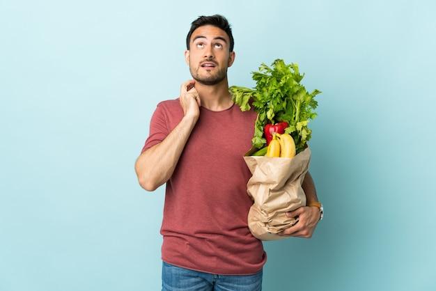 Jovem homem caucasiano comprando alguns vegetais isolados em uma parede azul pensando uma ideia