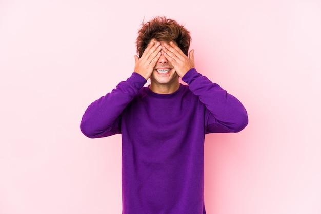 Jovem homem caucasiano contra um fundo rosa isolado cobre os olhos com as mãos, sorri amplamente esperando por uma surpresa.