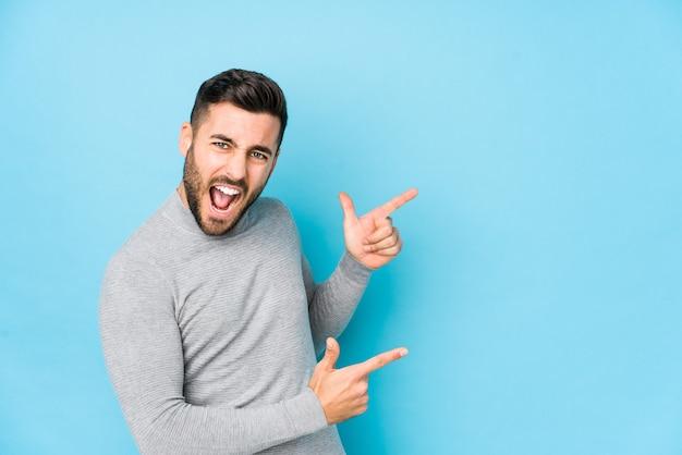 Jovem homem caucasiano contra uma parede azul isolada apontando com os indicadores para um espaço de cópia, expressando entusiasmo e desejo.