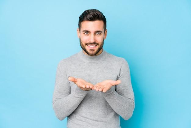 Jovem homem caucasiano contra uma parede azul isolada segurando algo com as palmas das mãos, oferecendo