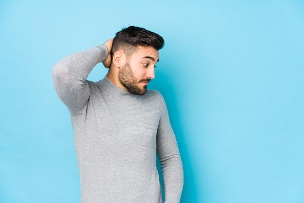 Jovem homem caucasiano contra uma parede azul isolada tocando a parte de trás da cabeça, pensando e fazendo uma escolha.