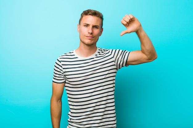 Jovem homem caucasiano contra uma parede azul, mostrando um gesto de antipatia, polegares para baixo. conceito de desacordo.