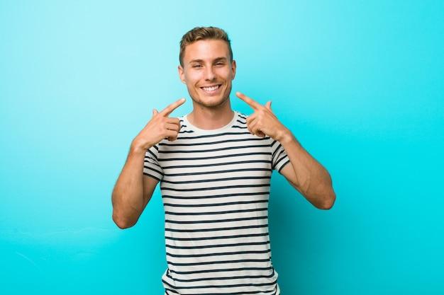 Jovem homem caucasiano contra uma parede azul sorri, apontando os dedos na boca.