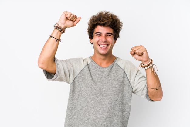 Jovem homem caucasiano contra uma parede branca isolada comemorando um dia especial, saltos e levante os braços com energia.