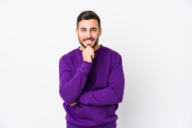 Jovem homem caucasiano contra uma parede branca isolado sorrindo feliz e confiante, tocando o queixo com a mão.