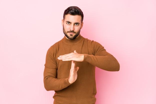 Jovem homem caucasiano contra uma parede rosa isolada, mostrando um gesto de tempo limite.
