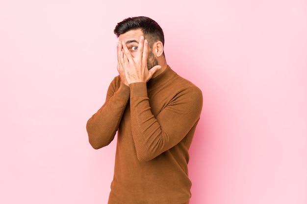 Jovem homem caucasiano contra uma parede rosa isolado piscar através dos dedos assustado e nervoso.