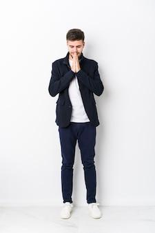 Jovem homem caucasiano de corpo inteiro isolado de mãos dadas orando perto da boca, sente-se confiante.