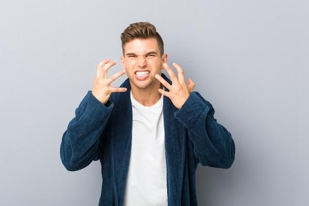 Jovem homem caucasiano de pijama chateado, gritando com as mãos tensas.