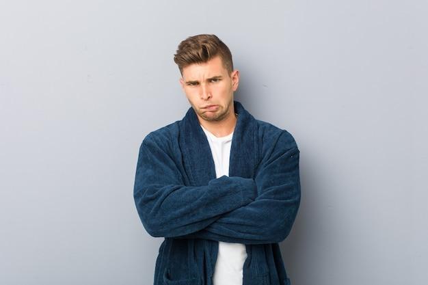 Jovem homem caucasiano de pijama, franzindo a testa em desgosto, mantém os braços cruzados.